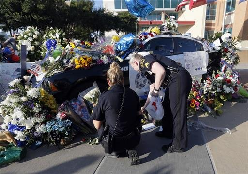 (AP Photo/Tony Gutierrez). Dallas police Sgts. Amanda Renteria, left, and Laura Browning right, add to a makeshift memorial in Dallas, TX.