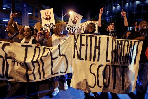 (AP Photo/Chuck Burton). Protesters shout as they march in the streets of Charlotte, N.C. Friday, Sept. 23