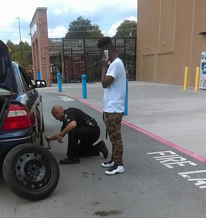 Ofc. David Stanley helps change car tire. (Source: Jayme Correia)