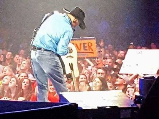Garth gives the signed guitar  (Courtesy: Tonya Dill)