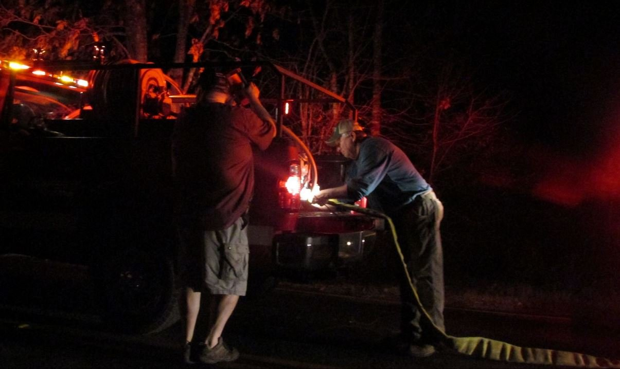 Firefighters connect a hose to a brush truck (Courtesy: Lacie Smith/ Salem Westhead)