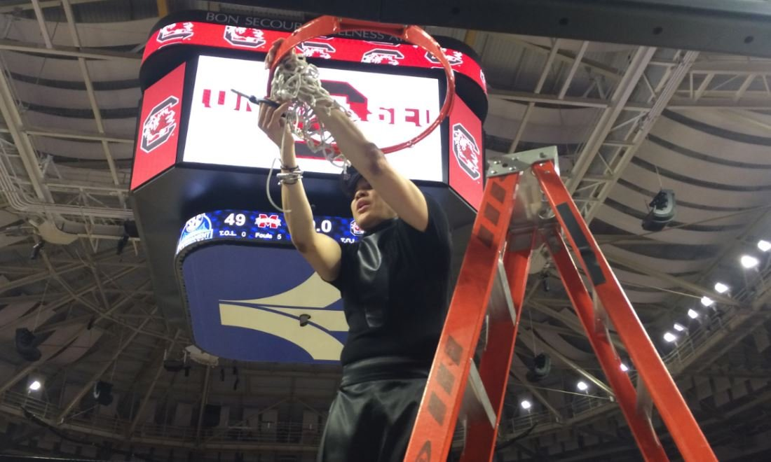Dawn Staley cuts down the net after USC wins the SEC tournament in Greenville (FOX Carolina)