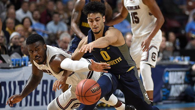 South Carolina's Duane Notice, left, and Marquette's Markus Howard, right, chase a loose ball during the second half in a first-round game of the NCAA. (Source: AP Images)