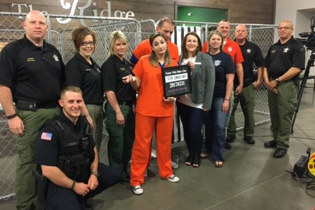 Alexa Rodriguez and Alex Schumann (center) pose with deputies during the Jail & Bail fundraiser (March 31, 2017/ FOX Carolina)