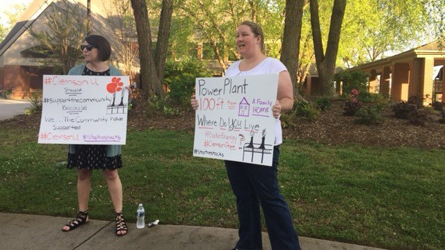 Signs being held outside open forum on Duke Energy power plant. (April 10, 2017 FOX Carolina)