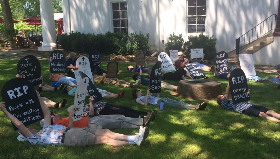 Demonstrators hold a die-in outside Graham's Pendleton office (May 9, 2017)