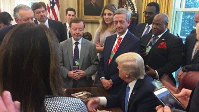 Pastor Mark Burns and others stand around President Trump in the Oval Office (Source: Pastor Mark Burns)
