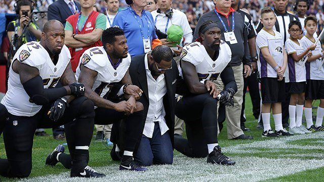 Members of the Baltimore Ravens kneel during the national anthem before an NFL game in London. (AP Photo)