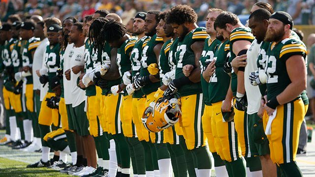Green Bay Packers lock arms during the national anthem (Source: Associated Press)