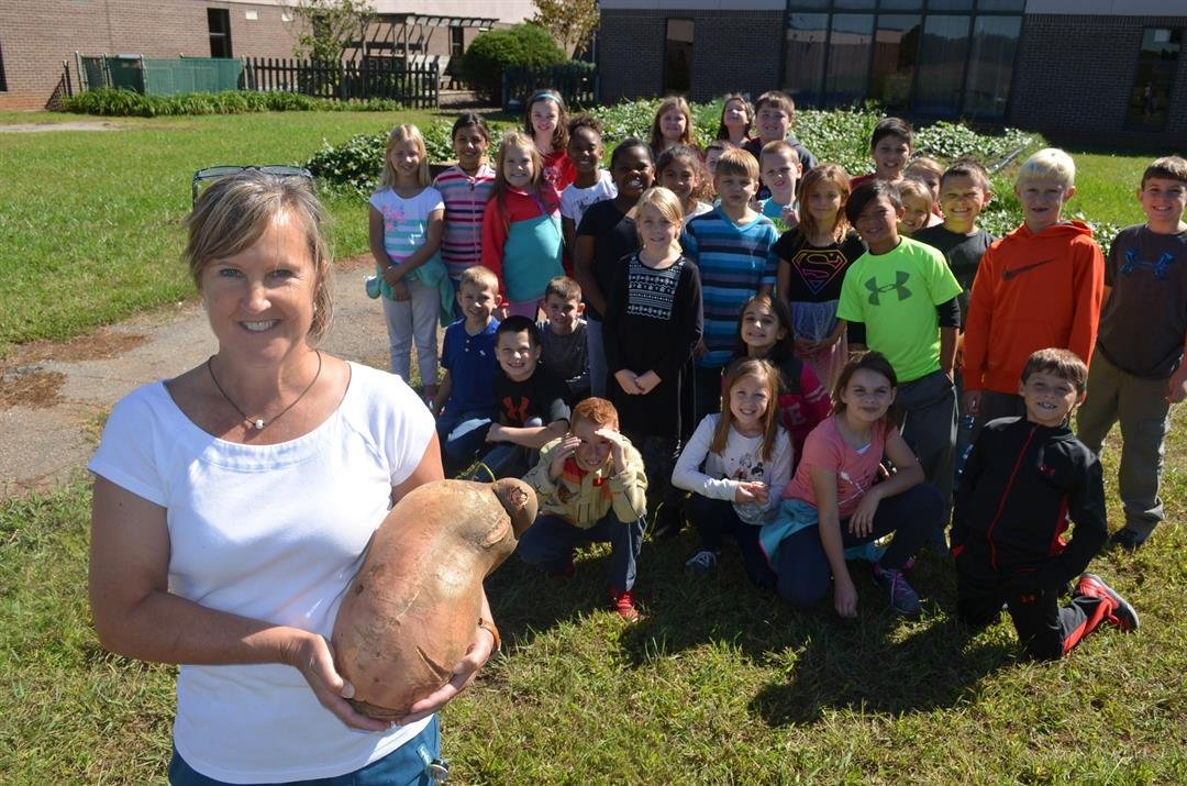 Nurse Hendrix holding the record potato in front of the school's garden while being cheered on by C-FG students. (Source: School district)
