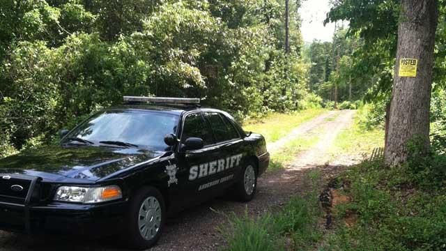 A deputy's cruiser blocks a road leading to where a body was found. (Aug. 9, 2011/FOX Carolina)