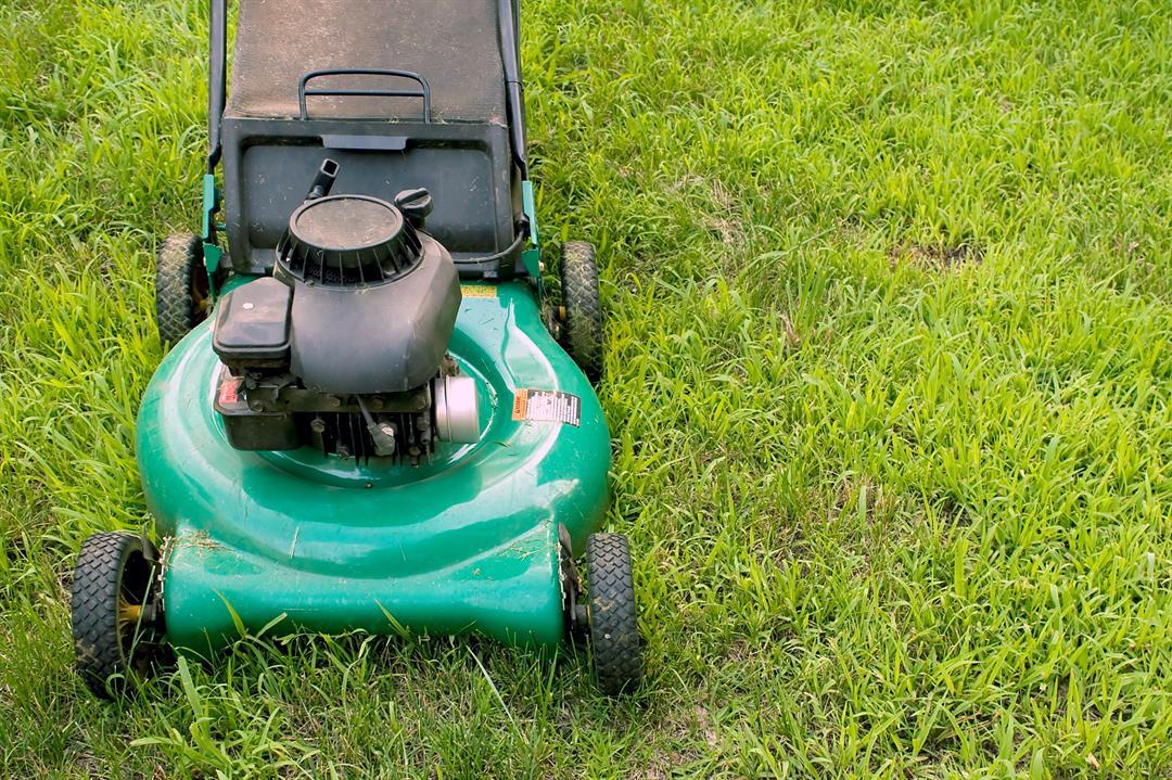 A modern lawn mower cutting through the grass (Storyblocks)
