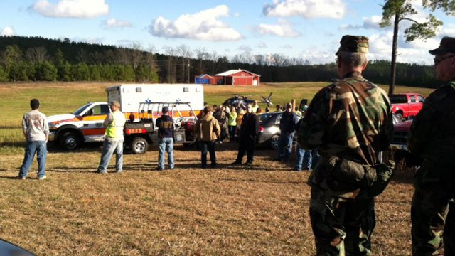 Search crews look on while Jason is loaded into an ambulance after being found alive. (Dec. 17, 2011/FOX Carolina)