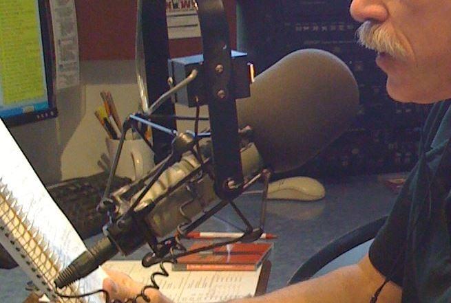 A DJ speaks into a radio studio microphone (Wikimedia Commons)