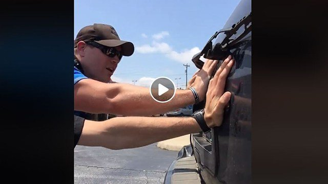 Ofc. Miller pushes car after driver ran out of gas (Source: GPD)