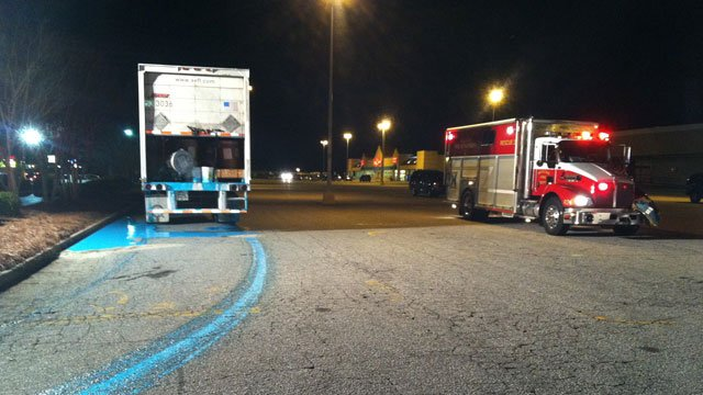 A blue liquid is seen leaking from the trailer of a semi in a Mauldin parking lot. (Feb. 27, 2012/FOX Carolina)