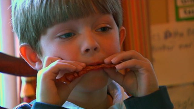 Giles Martin Schanen eats a piece of bacon, one of the few types of foods he is able to eat without pain. (File/FOX Carolina)