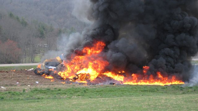 Flames and black smoke are seen rising from the runway at the Macon County Airport after a plane crashed. (March 15, 2012/Fred Bulgin)
