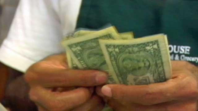 A restaurant worker counts cash given to him by a customer. (File/FOX Carolina)