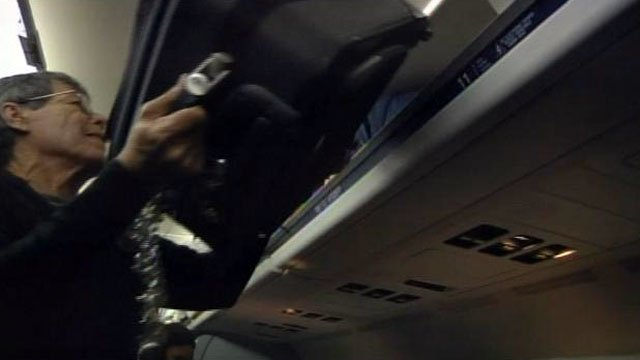 A passenger loads a carry-on bag into an overhead bin on an airplane. (File/FOX Carolina)