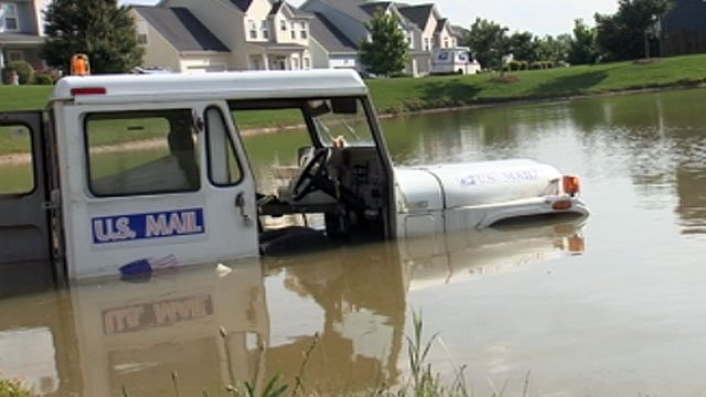 Part of a U.S. Postal Service truck is under water after rolling into a pond. (May 8, 2012/FOX Carolina)
