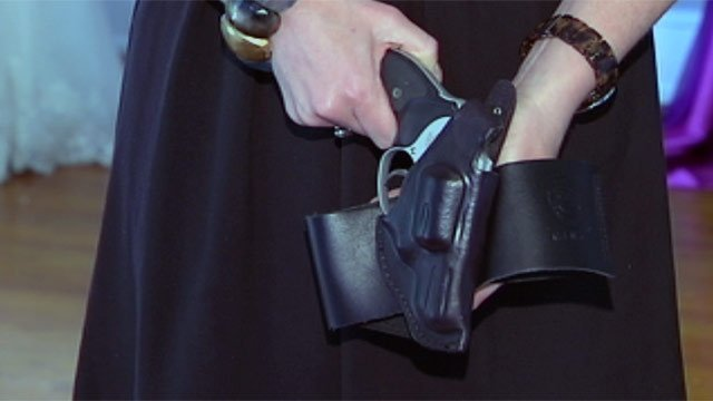 Leanne McBride holds her gun and holster that she wears around her leg. (June 11, 2012/FOX Carolina)