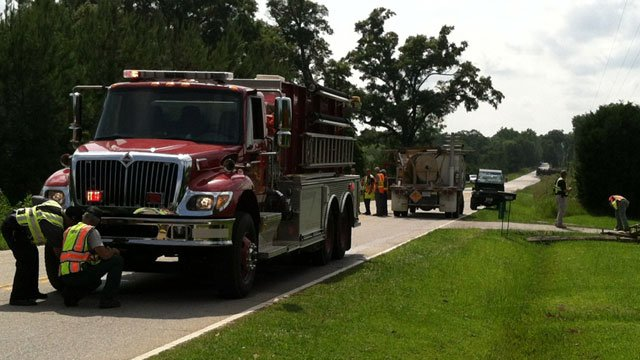 An overturned truck can be seen in the distance as emergency workers block off a highway. (June 12, 2012/FOX Carolina)
