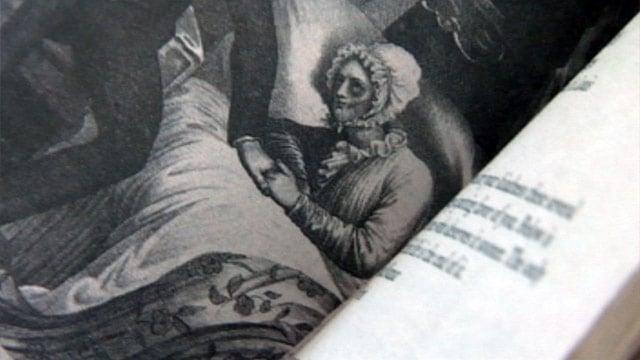 Professor Burton flips through the pages of Abraham Lincoln, Vampire Hunter. (June 18, 2012/FOX Carolina)