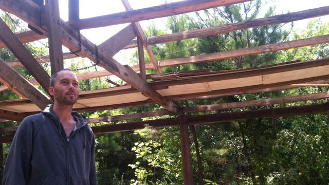 Jody Clary stands under his dad's shop that is now without a roof because of thieves. (June 21, 2012/FOX Carolina)