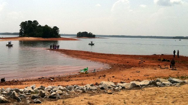 Emergency crews stand on the shores of Lake Hartwell while boats comb the water. (July 4, 2012/FOX Carolina)