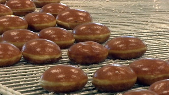 Krispy Kreme doughnuts roll through glaze at a local shop. (File/FOX Carolina)