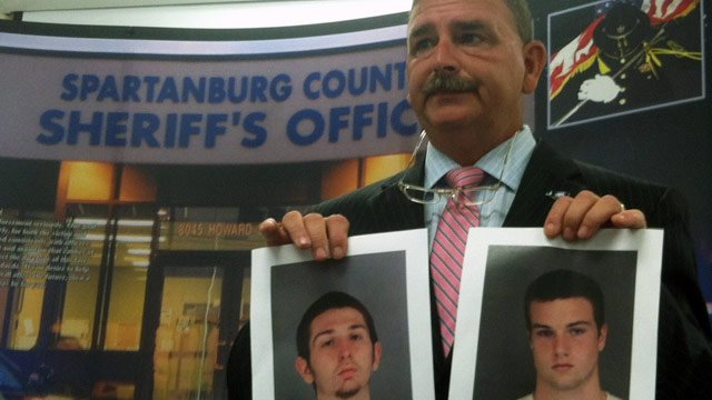 Sheriff Chuck Wright holds up photos of the suspects during Thursday's press conference. (July 12, 2012/FOX Carolina)