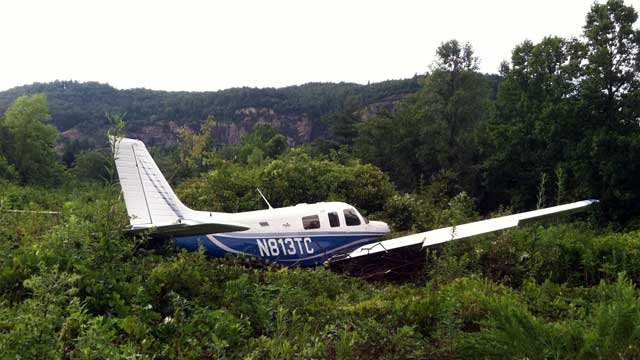 An airplane lays in a wooded area after the plane ran of the runway at a Brevard airport. (July 16, 2012/FOX Carolina)