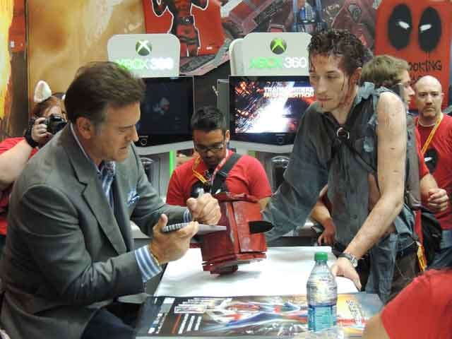 B movie Icon Bruce Campbell signing for a fan at the Activision Booth.