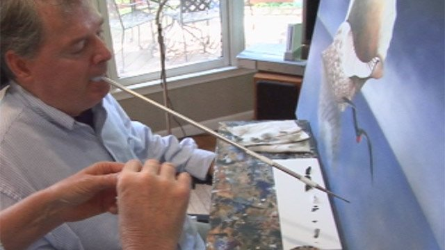 Marcus Thomas uses his mouth to control the paintbrush. (File/FOX Carolina)
