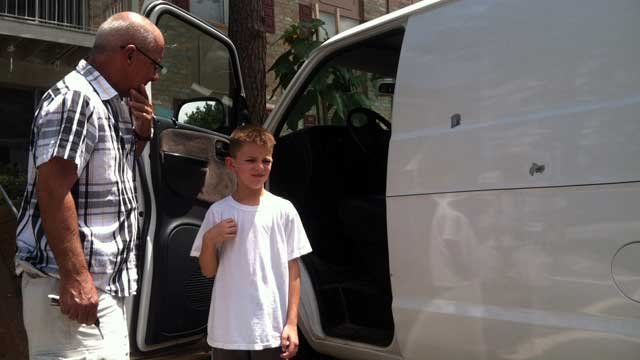 James Evans (left) and his grandson show the bullet holes left behind in Evans' van. (July 23, 2012/FOX Carolina)