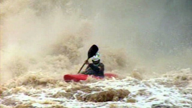 A kayaker paddles to the shore after tumbling down Reedy River Falls. (July 31, 2012/FOX Carolina)