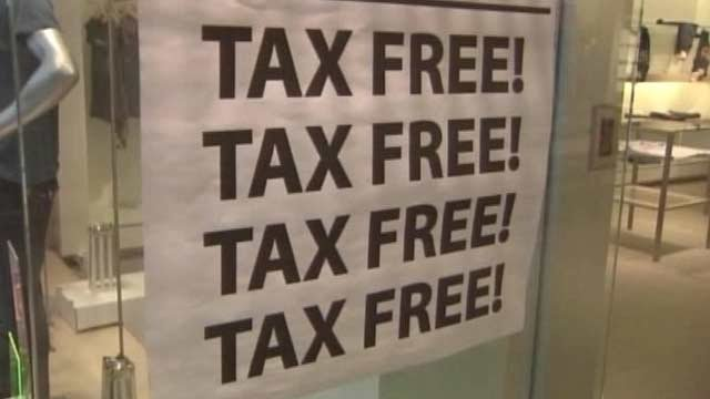 A sign hanging in a Greenville clothing store's window promotes the tax-free weekend. (File/FOX Carolina)