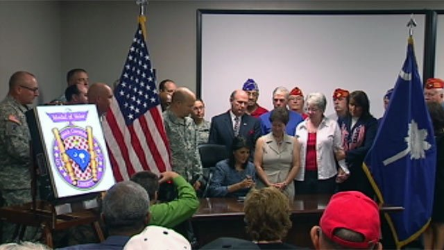 Veterans and supporters surround Gov. Haley as she signs the bill. (Aug. 21, 2012/FOX Carolina)