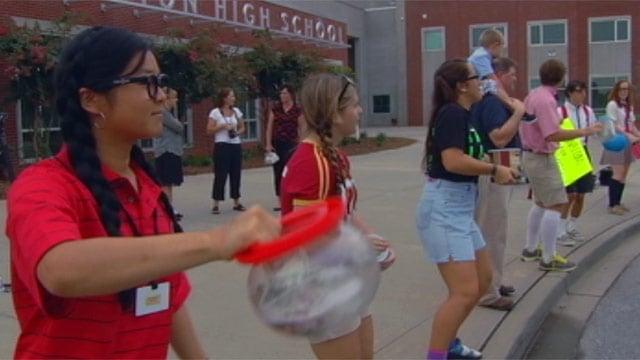Wade Hampton High students collect money in the carpool drop off line. (Sept. 5, 2012/FOX Carolina)