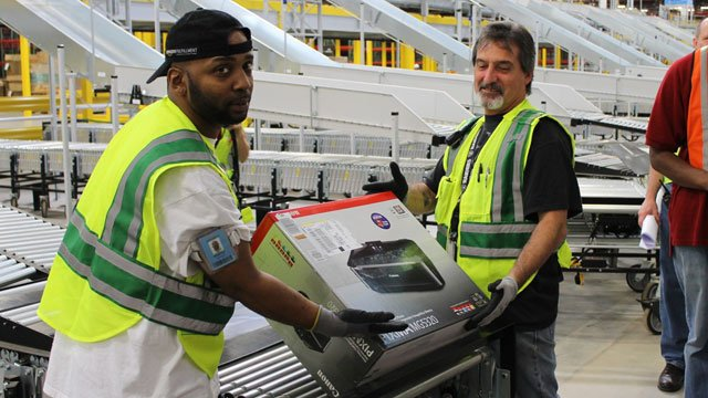 Two workers at Amazon's Spartanburg facility lift the warehouse's first order off a conveyer belt. (Sept. 20, 2012/McAlister Communications)