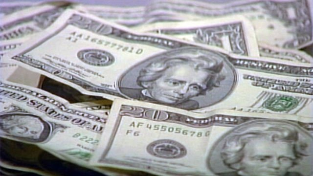 A pile of various denominations of bills appears on a table. (File/FOX Carolina)