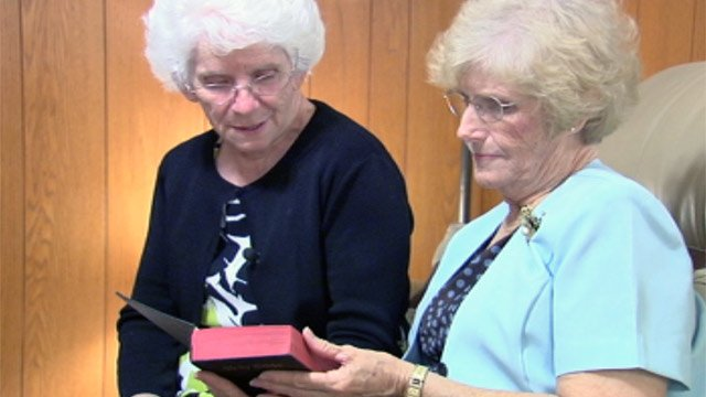 Pastor Karen Durham (left) and her sister Hazen Bernice George read their father's Bible that was missing since WWII. (File/FOX Carolina)