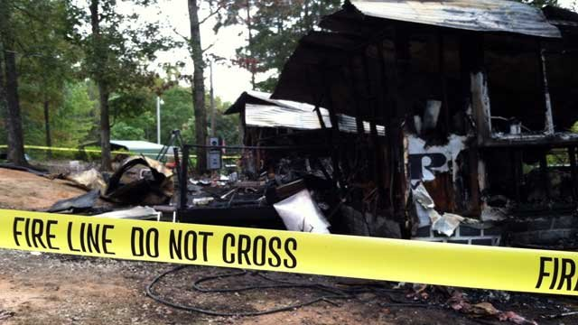 Fire-line tape surrounds a Walhalla mobile home after it was destroyed by fire. (Oct. 8, 2012/FOX Carolina)
