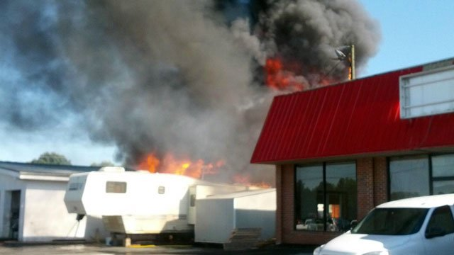 Flames and smoke billow from a building at a Spartanburg car dealership. (Oct. 16, 2012/FOX Carolina iWitness Jennifer Ash)