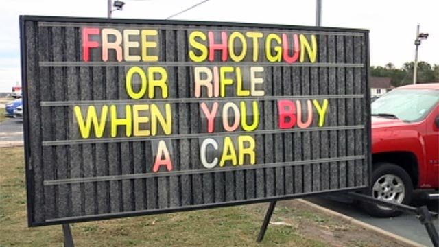 A sign outside a car dealership in Easley, SC, promotes a deal that allows car buyers to receive a free gun. (Oct. 30, 2012/FOX Carolina)