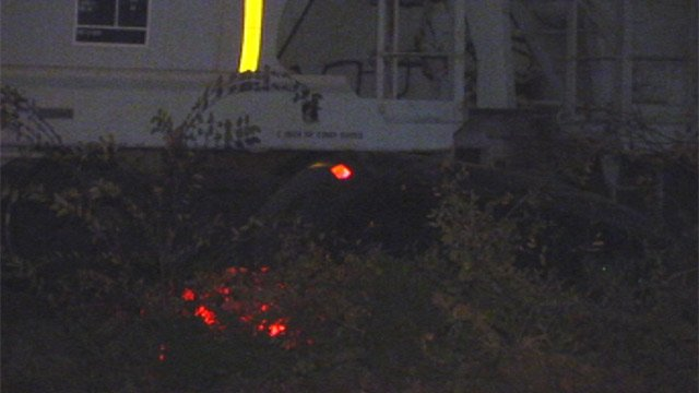The car's tail lights seen through the brush after being hit by the train. (Nov. 9, 2012/FOX Carolina)