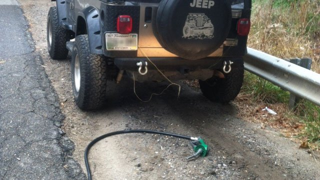 Police say this gas nozzle and hose was hanging from this Jeep when it was stopped. (Nov. 27, 2012/Asheville Police Dept.)