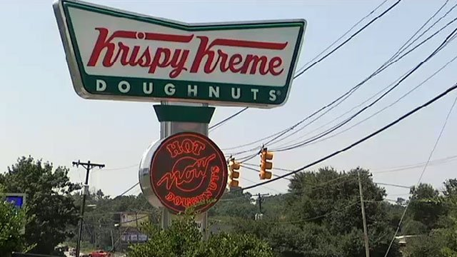 A Krispy Kreme sign is seen outside a location in Greenville. (File/FOX Carolina)