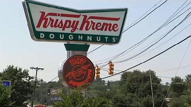 A Krispy Kreme sign is seen outside a location in Greenville. (File/FOX Carolina)